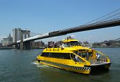 Watertaxi van New York City onder de Brooklyn Bridge