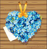 Abstract Classical Greeting card with floral heart. Heart from forget-me-not flowers on the wooden background.