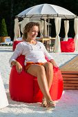 Beautiful girl sits on a soft red pufe in open air cafe