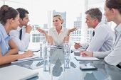 Businesswoman gesturing as she ignores something during a meeting
