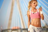 Stunning young blonde woman in pink sports bra rests and adjusting music on portable music player - smiling - fitness