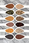 Seed food selection in white porcelain spoons over marble background.