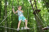 young happy child boy in adventure park in safety equipment