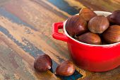 Chestnut In Red Bowl On Wooden Table