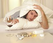 stock photo of hangover  - exhausted young Man in bed with coffee water and tablets suffering hangover and headache - JPG