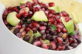 stock photo of cilantro  - A healthy relish or salsa with pomegranate avocado red onions black beans and cilantro served with corn chips - JPG