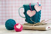Blue cup in a blue sweater with felt hearts
