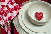 pic of xoxo  - tight shoot of white plates and bowl sitting on a silver charger. Red heart with XOXO on it in bowl Heart napkin with crystal butterfly napkin ring