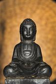 picture of metal sculpture  - Metallic Asian Buddha statue of a seated Buddha meditating in the lotus position against a mottled brown background