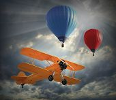 Retro style picture of the biplane and hot air balloons. History of aviation concept.
