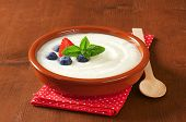 semolina pudding with fresh strawberries and blueberries, served in the ceramic bowl with dotted lin