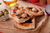 Slices of italian onion pizza with black olives
