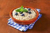 ceramic bowl with blueberry oatmeal, decorated with mint