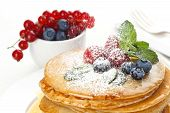 Small Pancakes Topped With Honey, Red Currants And Bilberries With Powdered Sugar On White Backgroun