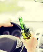 transportation and vehicle concept - man drinking alcohol while driving the car