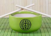 Green Teapot And Chopsticks On Straw Background