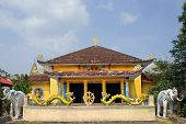 Yellow Pagoda on blue sky background with standing on the edges of the entrance sculptures of elepha