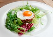 Beef tartar with fried egg and lettuce in plate