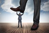 Composite image of businessman stepping on tiny businessman against cloudy sky background