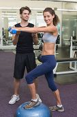 Fit woman stepping on bosu ball holding dumbbell with trainer at the gym