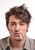 Young man with particular hair style portrait smoking cigarette.