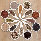 Large super food seed selection in porcelain bowls over light oak background.