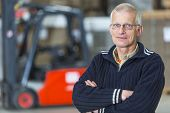 A forklift driver is posing in front of his forklift, he is a proffesional forkliftdriver, working i