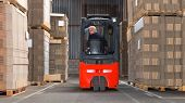 foto of forklift driver  - Expreinced forklift driver is driving his forklift backwards trough piled pallets with  cardboardboxes stack on it - JPG
