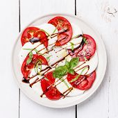 Caprese Salad Tomato And Mozzarella Slices With Basil Leaves On White Wooden Background