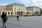 KRAKOW, POLAND - SEPTEMBER 15, 2013: People waiting, resting and walking in front of the main train station. Opened in 1847, the building was underground expanded in 2000s