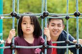 stock photo of take responsibility  - Father is taking care about his daughter on the playground - JPG