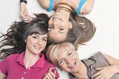 foto of braces  - Portrait of Happy Caucasian Girls Wearing Teeth Braces Lying Together with Heads In Center - JPG