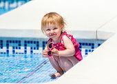 smiling cute little baby swims  in the pool in  summer