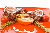 meat savory: roast ribs on red plate with peppers and rosemary