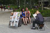 Unidentified tourists posing for street artist in Manhattan