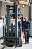 The forkliftdriver standing next to his forklift in a large warehouse, full of boxes, posing