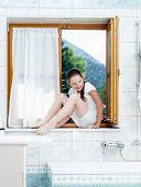 Teenage Girl Sitting On Bathroom Window