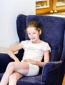 Cute Teenage Girl Sitting In Arm-chair