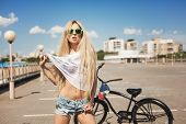 stock photo of swag  - Young woman standing next to black bicycle - JPG
