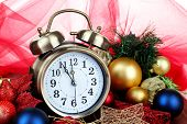 Alarm clock with Christmas decorations on table on red cloth background