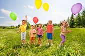 Five cute children with balloons in green field
