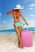 Slim tall woman with luggage on white sand beach