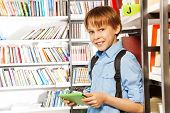 Cute boy stands and holds books in library