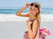 Smiling blonde carrying bag and towel on the beach on a sunny day