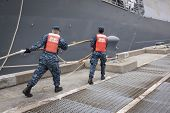 STATEN ISLAND, NY - MAY 21, 2014: Sailors from NWS Earle Port Services tend the lines of the guided-