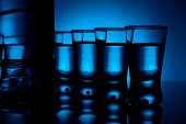Bottle Of Vodka With Many Glasses Lit With Blue Backlight