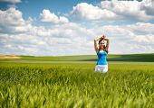Beautiful girl relaxing in a green wheat field standing with her arms raised above her head and a lo