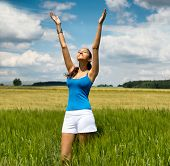 Young woman worshipping the hot summer sun as she stands in a scenic green field with her arms raised, head tilted to the sunshine and a smile of bliss, with copyspace
