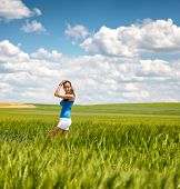 Pretty young girl in white summer shorts standing sideways in a green wheat field under a blue sky w