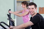 Couple Exercising At Fitness Gym